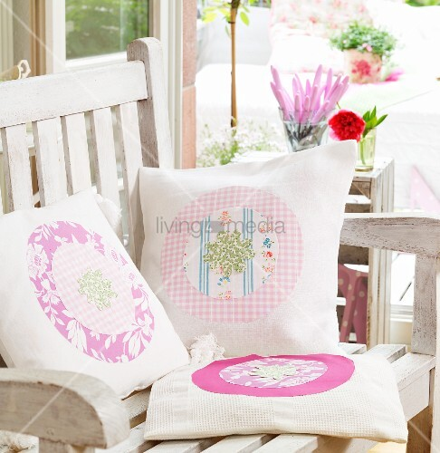 Hand-sewn scatter cushions with various patterns and appliqué motifs on wooden garden chair
