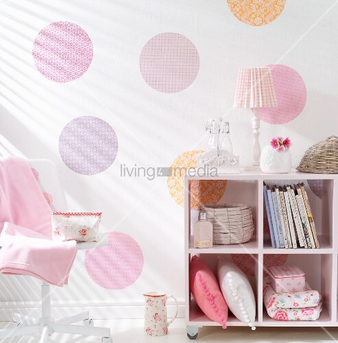 Half-height cabinet on castors in romantic, feminine interior with hand-crafted pattern made from pastel circles of wallpaper or gift wrap on wall