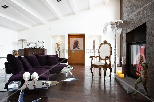 Modern, purple sofa and Rococo chair in front of artistically decorated open fireplace in open-plan loft interior with white-painted, ribbed ceiling
