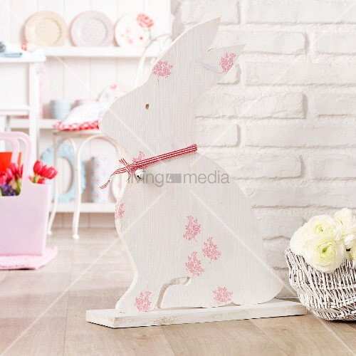 Hand-crafted, wooden Easter bunny in front of white brick wall
