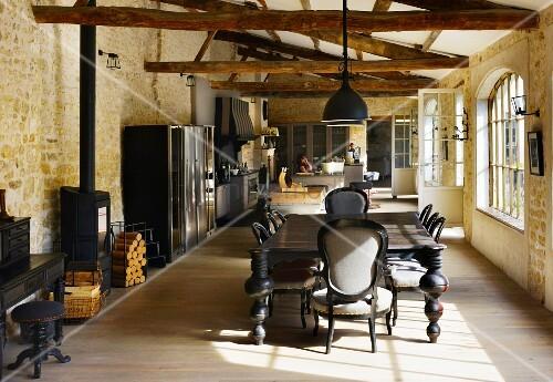 Teilrenovierte Scheune mit rustikaler Dachkonstruktion - Essplatz im Kolonialstil, dahinter Kochbereich in offenem Wohnraum