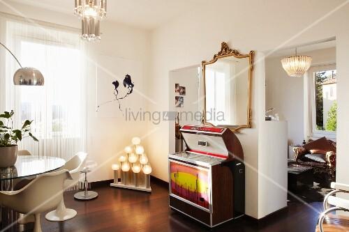 Retro Musikbox unter Goldrahmenspiegel, Essplatz mit Klassikerstühlen und ausgefallene Leuchtobjekte im Wohnraum