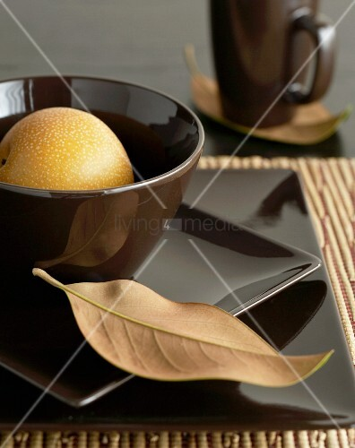 Place setting with brown square plates and dry leaf resting on plate