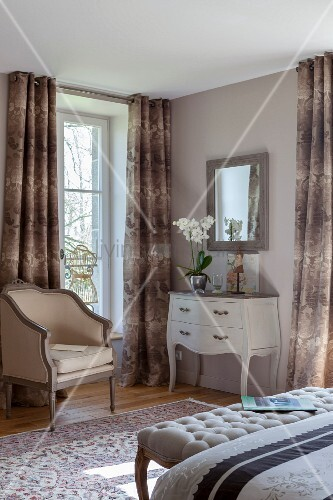 Antique armchair next to window with floor-length curtains and white console table in corner of bedroom