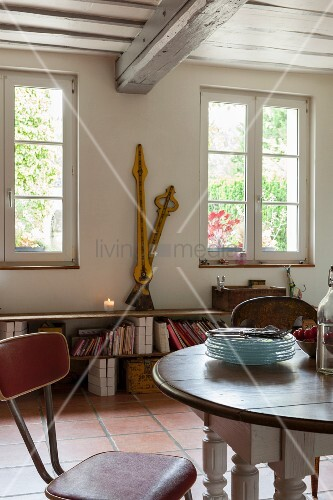 Dining area with retro chair and large vintage clock hands on bench in rustic, country-house interior