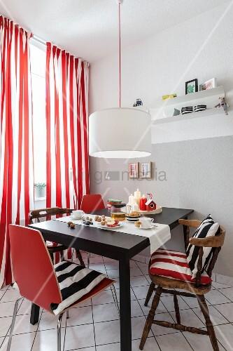 Essplatz mit alten und neuen Stühlen vor Fenster mit rot-weiss ...