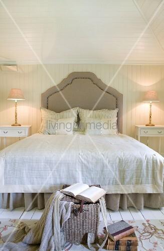 Doppelbett mit geschwungenem Kopfteil in hellem, holzvertäfeltem Landhaus Schlafraum