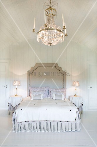 Opulent crystal chandelier above grand double bed in white-panelled bedroom