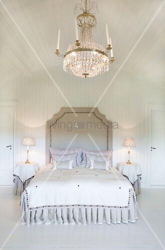 Opulenter Kristalleuchter über herrschaftlichem Doppelbett im weiss vertäfelten Schlafzimmer