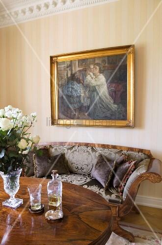 Ölgemalde über Biedermeier Sofa, weisse Rosen in Glaskelch und Aperitif auf Tisch im Vordergrund