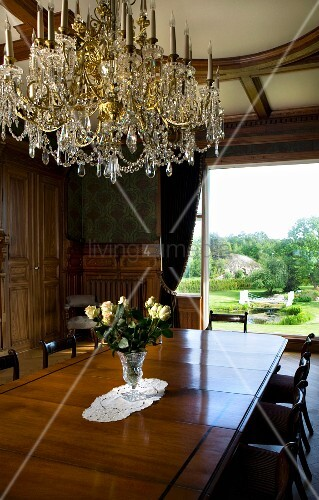 Crystal chandelier above long Biedermeier table in magnificent room with view of garden through panoramic window