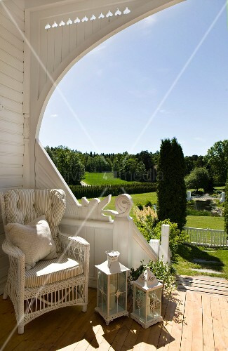 Wicker chair and lanterns in sheltered corner of exquisite wooden terrace with view of well-tended, landscaped garden
