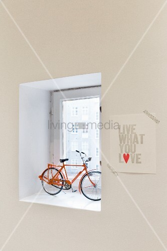 Model bicycle in window niche and motto stuck to wall with washi tape