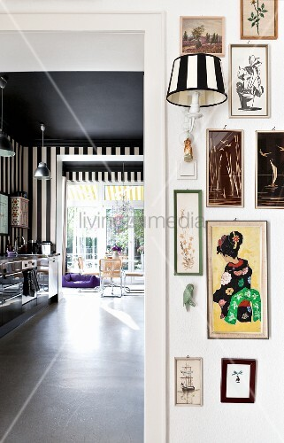 Eclectic collection of pictures and sconce lamp next to doorway with view into kitchen and dining area with black and white striped wallpaper and black-painted ceiling