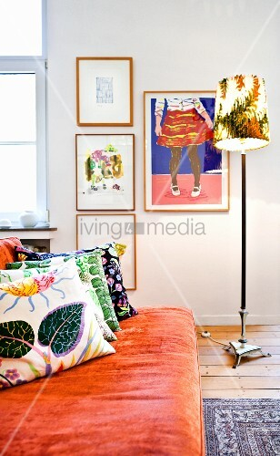 Patterned scatter cushions on orange sofa and standard lamp in front of gallery of pictures on wall