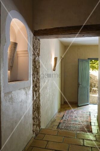 Beleuchtete Wandnische im Hausflur eines restaurierten, provenzalischen Gebäudes, Teppichläufer auf Fliesenboden