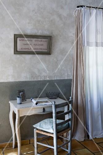 Textilbild mit Kräuternamen über kleinem, antikem Schreibplatz mit Geflechtstuhl, marmorierte Wände und Vorhänge in Naturfarben