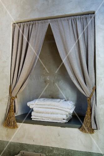 Nische mit drapiertem Vorhang in einer mit natürlicher Umbra patinierten Badezimmerwand