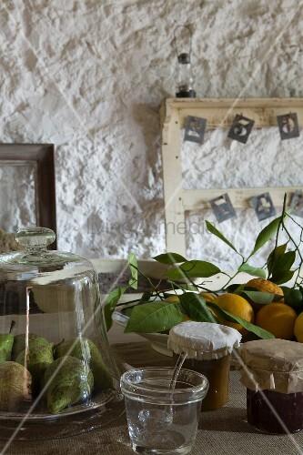 Birnen unter Glasglocke, frisch geerntete Zitronen und Marmeladengläser, alte Holzrahmen vor grob verputzter Wand
