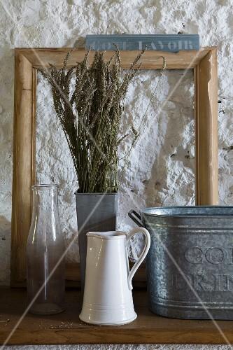 Stillleben mit Vintage Gefässen aus Zink, Emaille und Glas, Lavendel Trockenstrauss und Holzrahmen vor grob verputzter Wand