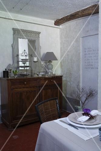 Alter Kommodenschrank mit Spiegel und gedeckter Tisch im Esszimmer mit weißem Kalkanstrich
