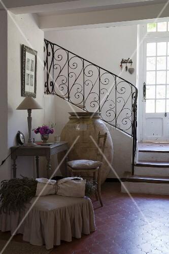 Kleiner, antiker Schreibplatz, riesiger, alter Olivenkrug und Polsterhocker mit Lavendelbündel vor Treppe mit schmiedeeisernem Geländer, Terrakottaboden