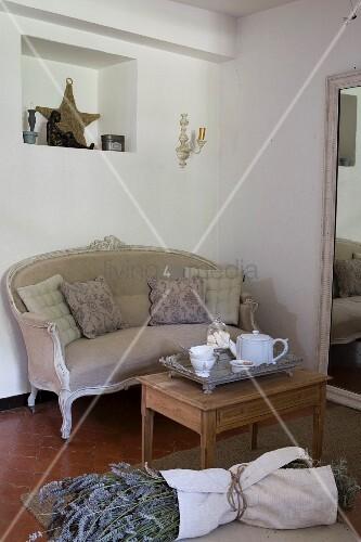 Abgebeizter alter Beistelltisch und antikes Canape vor Ankleidespiegel, Lavendelbündel im Vordergrund