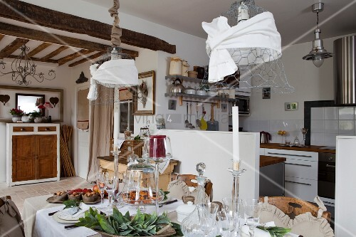 Festively set table below decorated, wire mesh pendant lamps in open-plan country-house interior