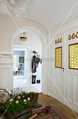 Türelement mit farbigen Butzenscheiben im Eingangsbereich, Holzkiste mit Geranien, Spaten und Gummistiefel vor Türbogen