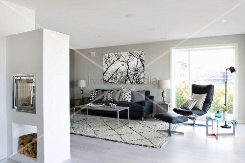 Masonry fire place in lounge area with grey-painted walls, black leather easy chair and footstool