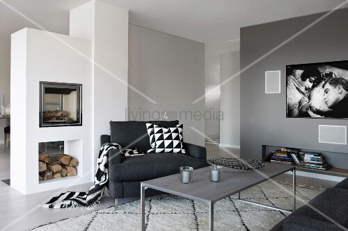 Grau getönter Loungebereich mit filigranem Couchtisch und schwarzer Sessel, seitlich gemauerter Kamin