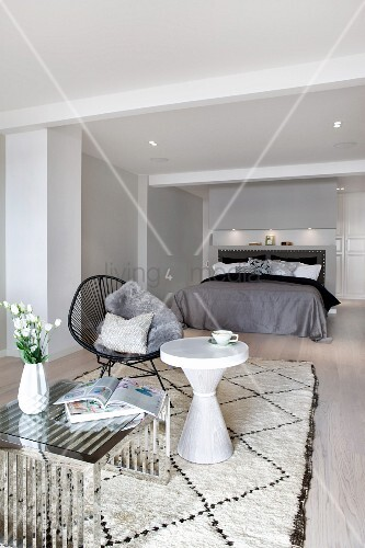 Chrome-framed coffee table, white side table and black easy chair on rug in front of double bed in minimalist bedroom