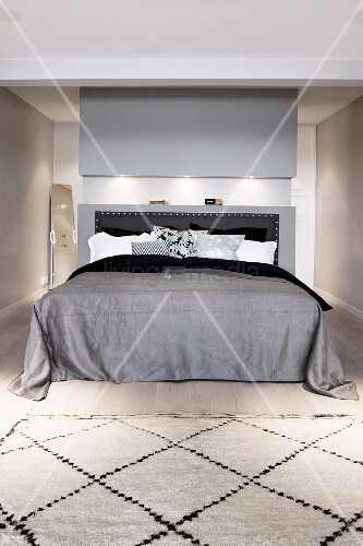 Double bed with grey bedspread, black headboard against grey-painted partition and Berber rug at foot