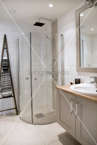 Washstand with base unit next to shower cubicle with curved glass wall in modern bathroom