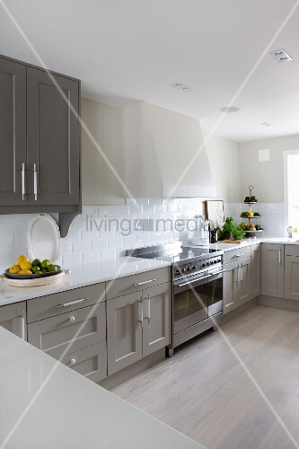 Kitchen counter with white worksurface and grey-painted base units in spacious kitchen