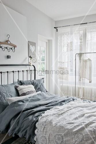 Bett mit grauer Bettwäsche und weisser Häkeldecke
