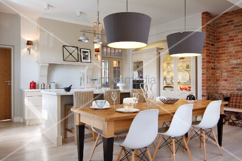 Classic chairs with white shell seats at wooden table below pendant lamps with grey, conical lampshades in front of white island counter in open-plan kitchen