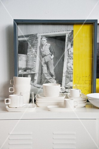 Hand-crafted, white cups and saucers on metal cabinet