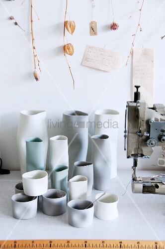 Handgefertigte Keramikvasen neben Nähmaschine auf Werkbank
