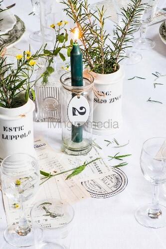 Brennende Kerze im Glas, weisse Porzellanvasen mit Kräutern auf Tisch