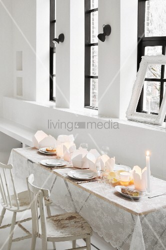 Table set with lace tablecloth and take-away cartons used as tealight holders in loft apartment
