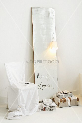 Christmas greeting on dull mirror, loose-covered chair and gifts wrapped in newspaper