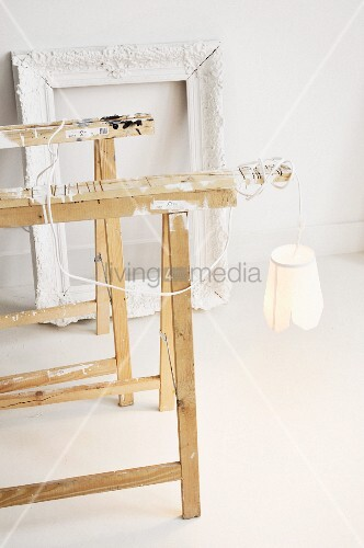 Lamp hanging from one of two painters' trestles in front of Baroque picture frame