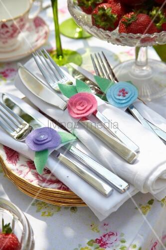 Selbstgenähte Serviettenringe aus pastellfarbenen Filzblumen mit romantischem Flair auf festlichem Gartentisch