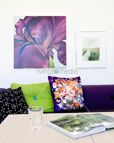 glas und aufgeschlagenes buch auf tisch vor sofa mit gemusterten kissen an wand bilder bild. Black Bedroom Furniture Sets. Home Design Ideas