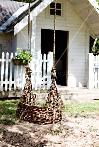 Aufgehängte Schaukel aus Weidenzweigen im Freien, im Hintergrund weisses Holzhaus