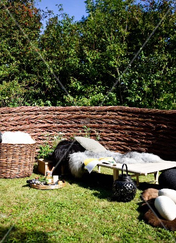 Idyllic relaxation area in garden; animal-skin blankets on sun lounger next to tray on lawn