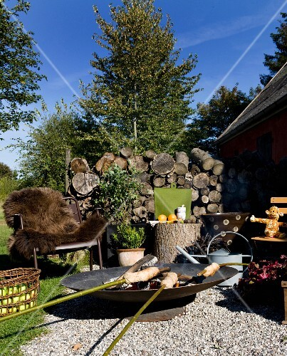 Campfire bread in fire bowl in front of outdoor metal armchair with brown fur blanket and stacked firewood on gravel terrace in garden