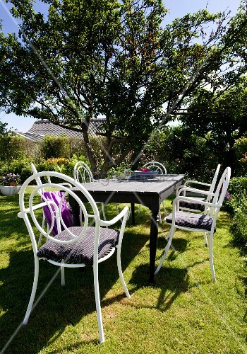 Wooden table and white chairs made from curved metal in summery garden
