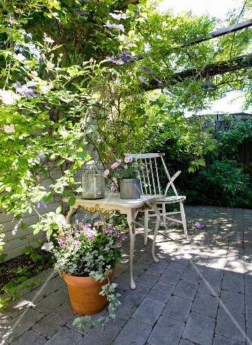 Summery terrace with climber-covered pergola, stone floor and vintage side table with curved legs